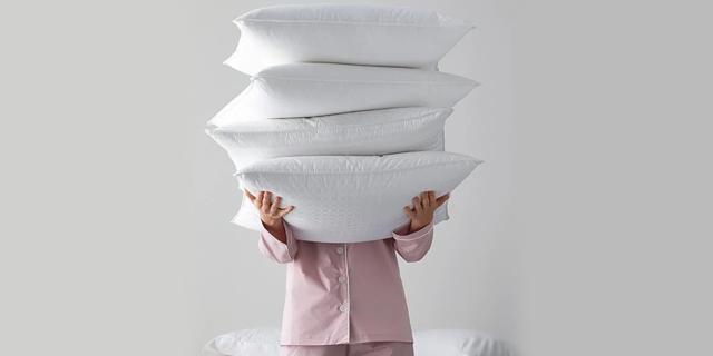 pessoa segurando muitos travesseiros