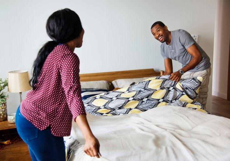 casal arrumando a cama
